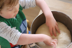 Ovi pulling bread dough apart during the kneading process on Ovi and Reu creative lifestyle blog