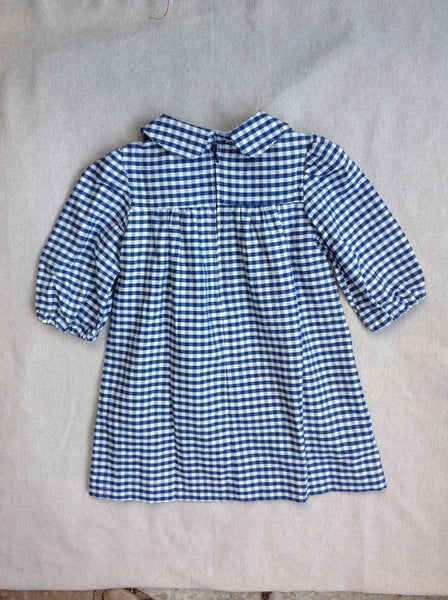 Blue dress in gingham check. Perfect gift for a little girl or children birthday present. Red detail across the chest. Handmade in Somerset by Runaround Retro and available with free deliver from Wonder of Kin.