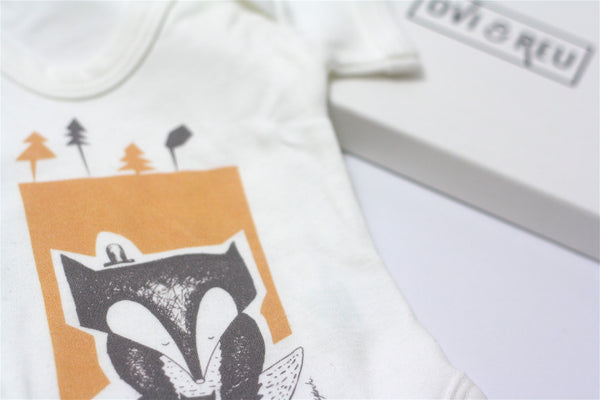 The Country Highlights Collection gift box for new and expectant mums contains a newborn fox baby vest. Available from Wonder of Kin - Curating Independent Brands.