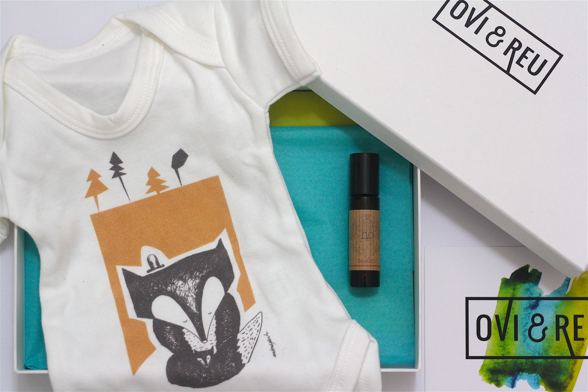 Ovi and Reu gift subscription box for new mums. The Newborn Box includes a fox baby vest and aromatherapy roller.