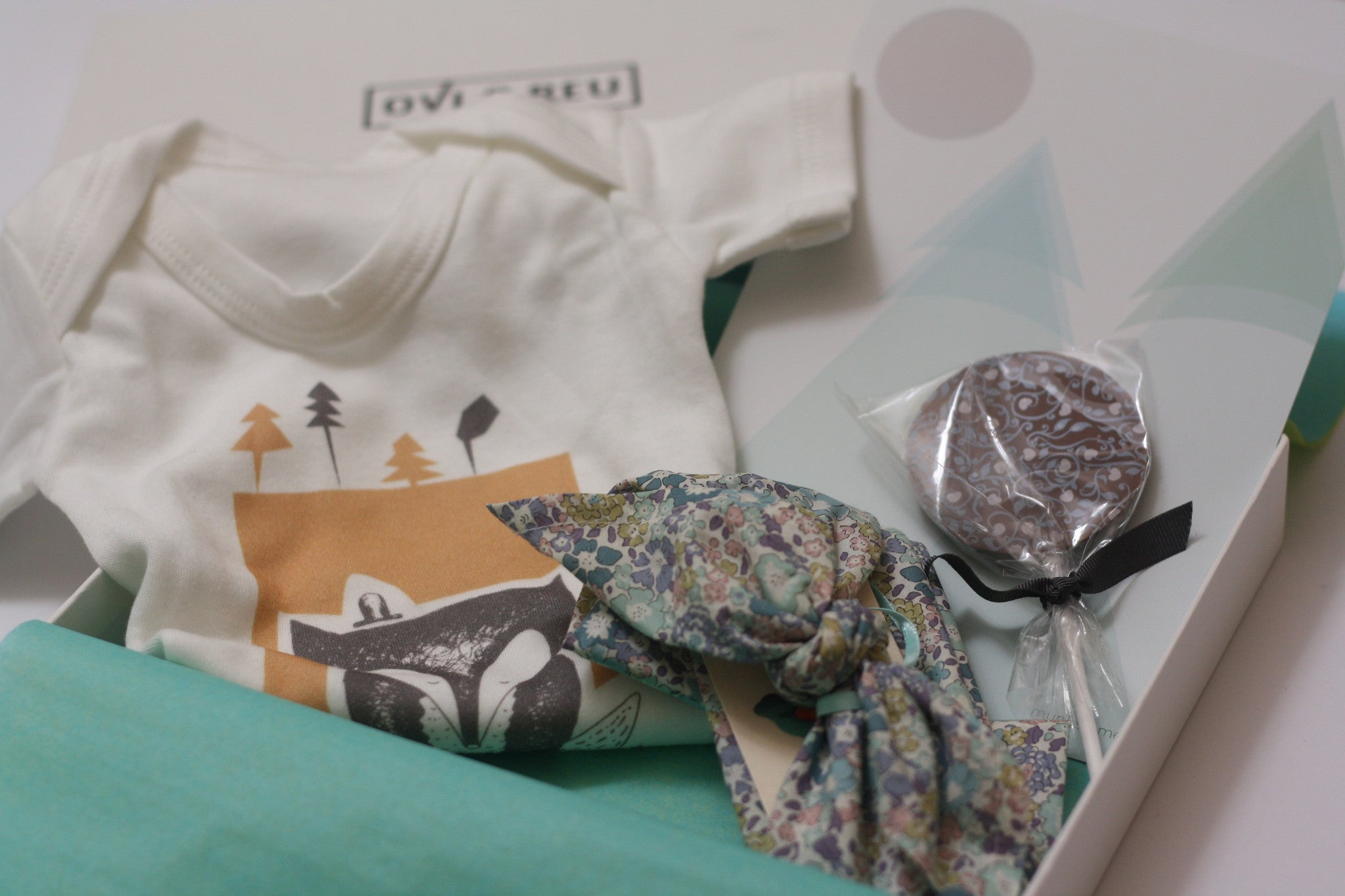 The Country Highlights Collection gift box for new and expectant mums from Ovi and Reu contains a fox baby vest, chocolate lolly, Liberty Print headscarf and mountains nursery print. Available from Wonder of Kin - Curating Independent Brands.