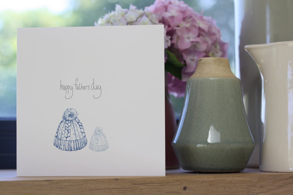Happy Father's Day card featuring hand drawn quirky bobble hat design. One large bobble hat in blue and a smaller, child's hat, in teal. Modern colours and a handmade quality which is quite beautiful. Designed and made by Gemma Louise Joyce exclusively for Wonder of Kin.