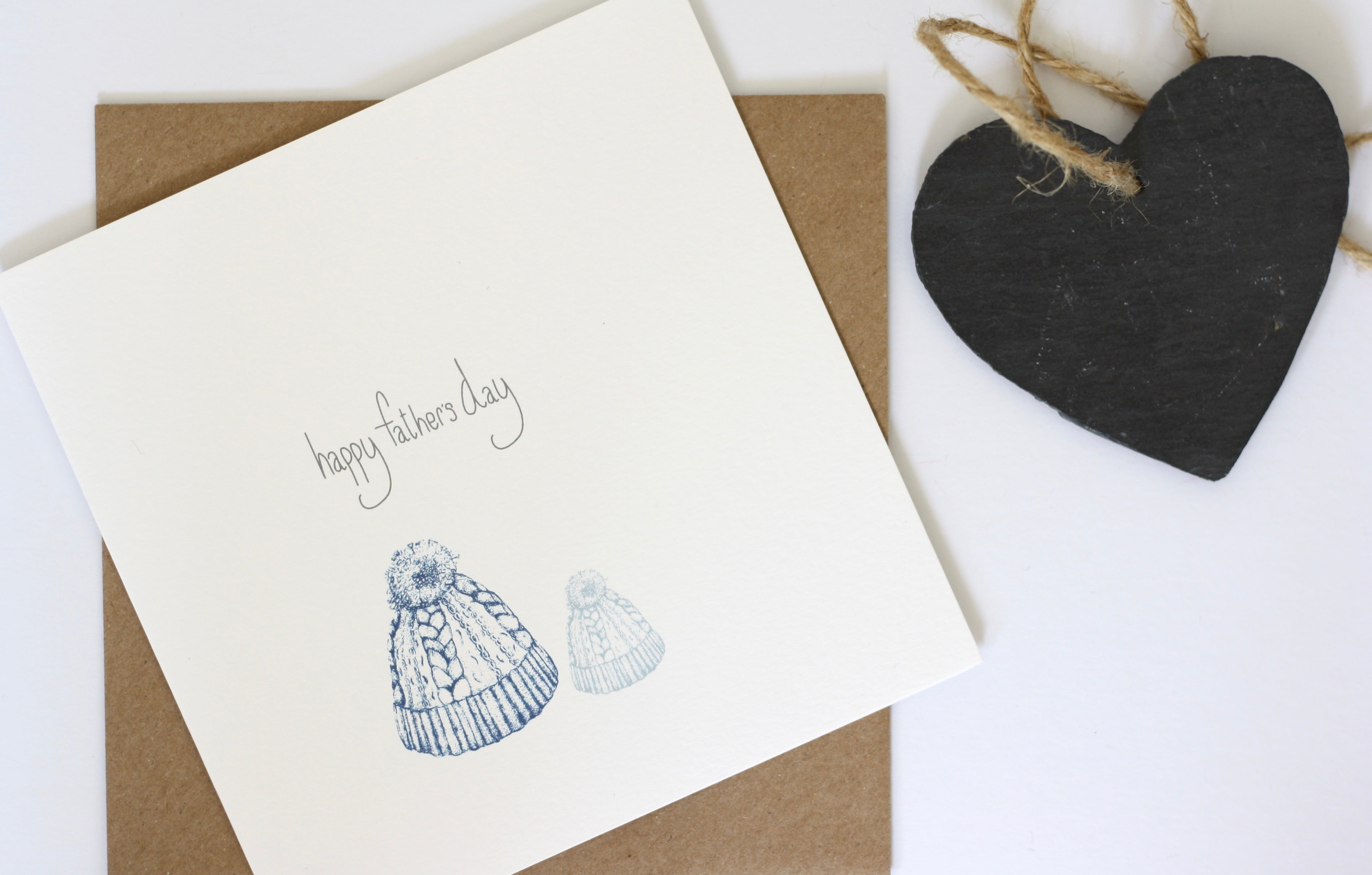 Happy fathers day card featuring a large and little, father and child bobble hat design hand drawn by Gemma Louise Joyce and available exclusively at Wonder of Kin.
