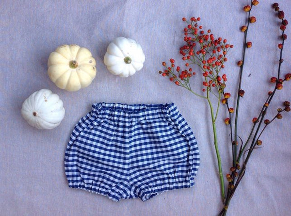 Red gingham check jumbo baby bloomers. Perfect gift for newborn or baby. Can be worn in summer with bare legs or in winter with tights underneath. Unisex gift for children and so on-trend! Made by hand in Somerset by Runaround Retro and available from Wonder of Kin with free delivery.