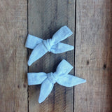 Set of two linen bows on clips for little girls. The perfect vintage addition to a child's outfit to bring some retro style. Wear with bunches or beneath buns or perfect for on the side of the head for a smaller child as the bows are smaller than the School Girl style. handmade by Runaround Retro and available with free delivery at Wonder of Kin.