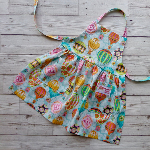 Mini Pinny for children learning to cook. Selection of full skirted pines in various bright colours available from Wonder of Kin - Curating Independent Brands.