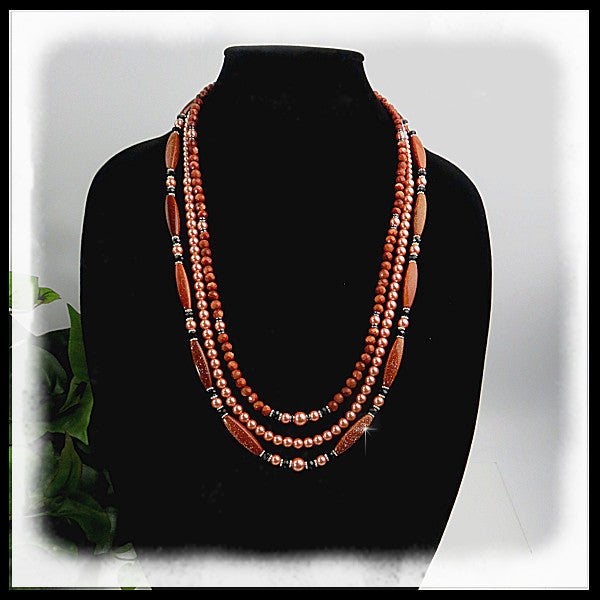 Triple strand of Goldstone with sterling silver beads and hook clasp.