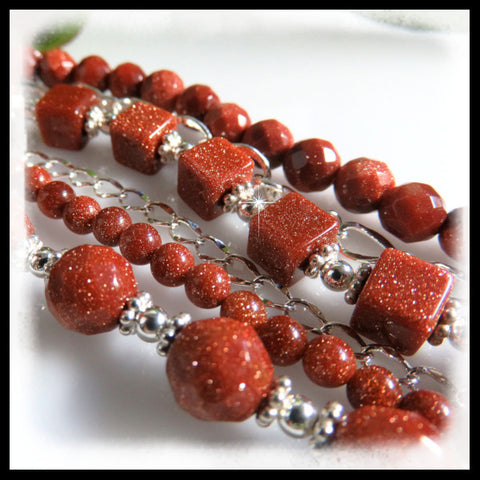 Six strand bracelet of goldstone beads and sterling silver chain.