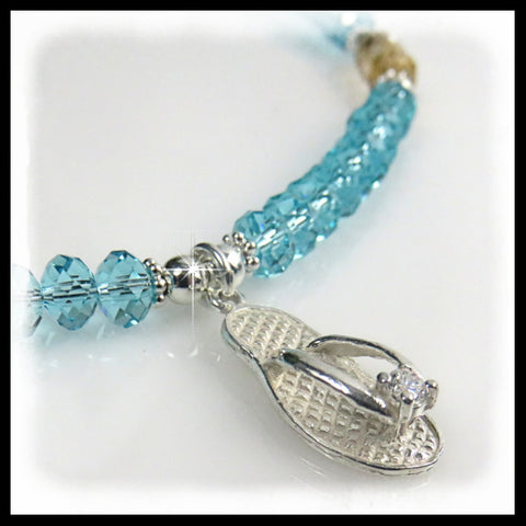 Sterling silver flip flop charm on light turquoise crystal necklace.