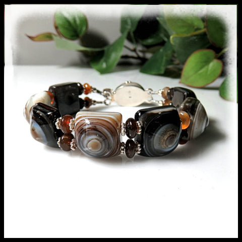"Squares of banded agate in a 1"" wide beaded bracelet with onyx clasp."