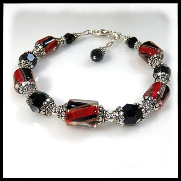 Elegant red and black David Christensen glass set in detailed sterling silver bead caps.
