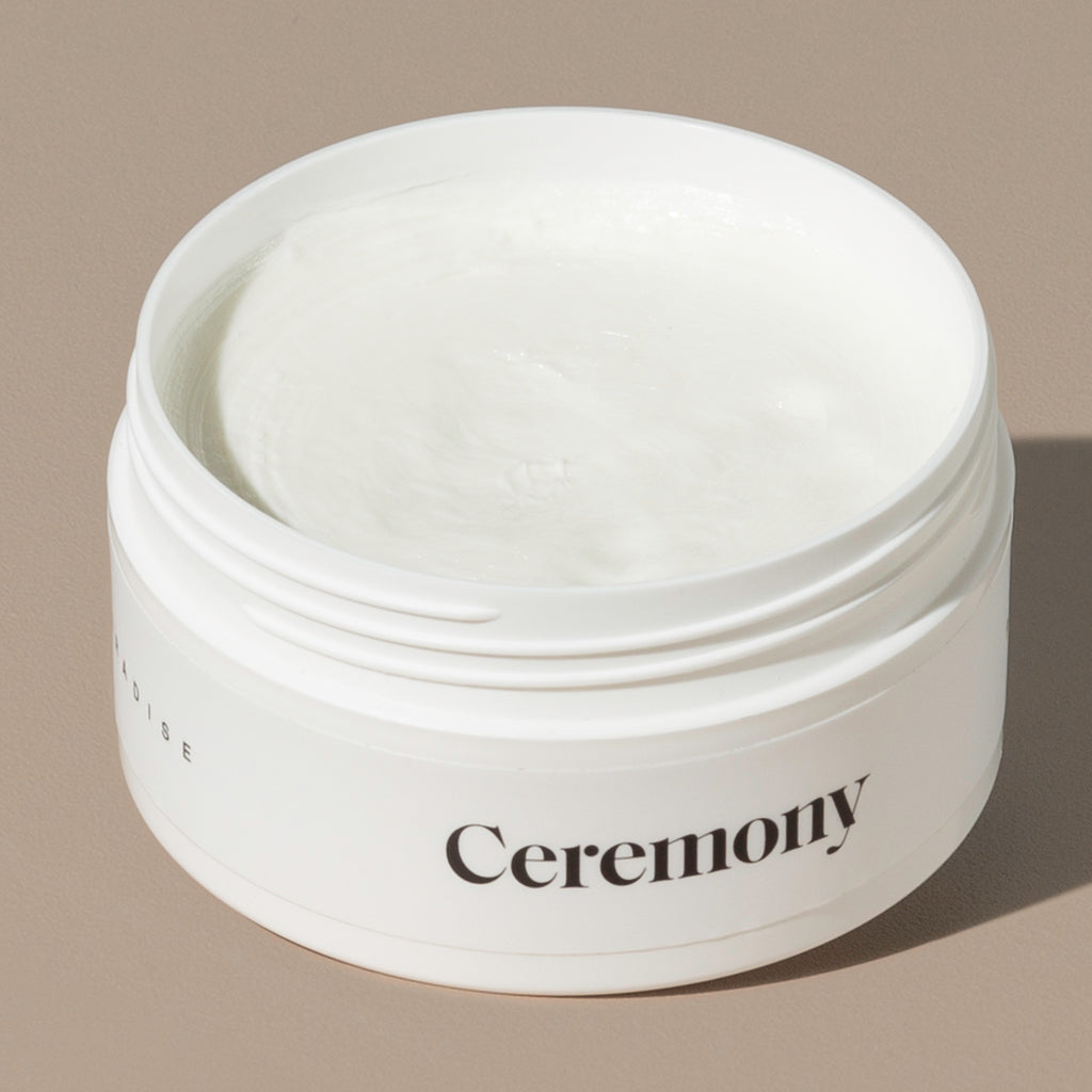 A view inside paradise pliable hair moulding cream which is in a white round plastic container with minimalist black labeling