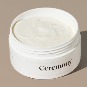 A view inside creamy Ceremony powder high hold hair pomade which is in a white round plastic container with minimalist black labeling