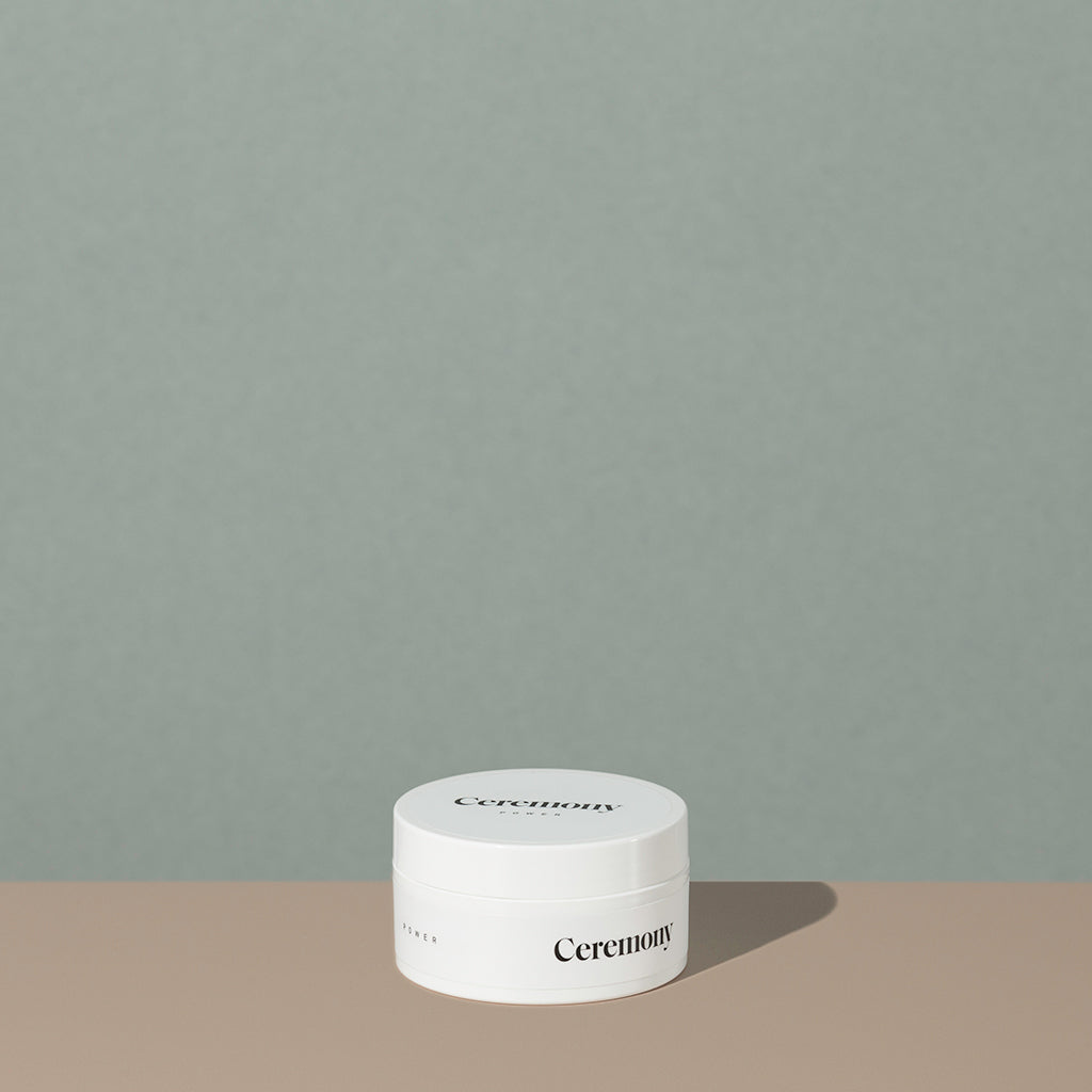 Ceremony powder high hold hair pomade in a white round plastic container with minimalist black labeling