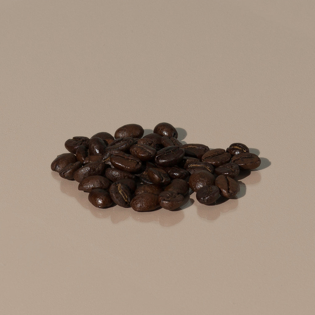 Emporium Espresso Blend by Cafellini small amount of dark brown roasted coffee grains on a table