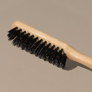 Details Close up of Groom black boar bristles beard or hair brush with idled clear beech wood handle
