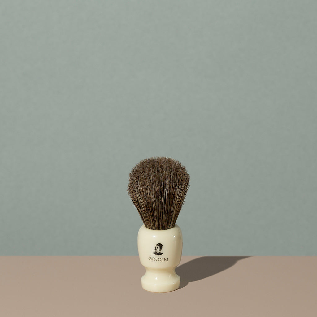 Groom shaving brush with brown horsehair bristles and cream off white acetate handle with black mustache man logo