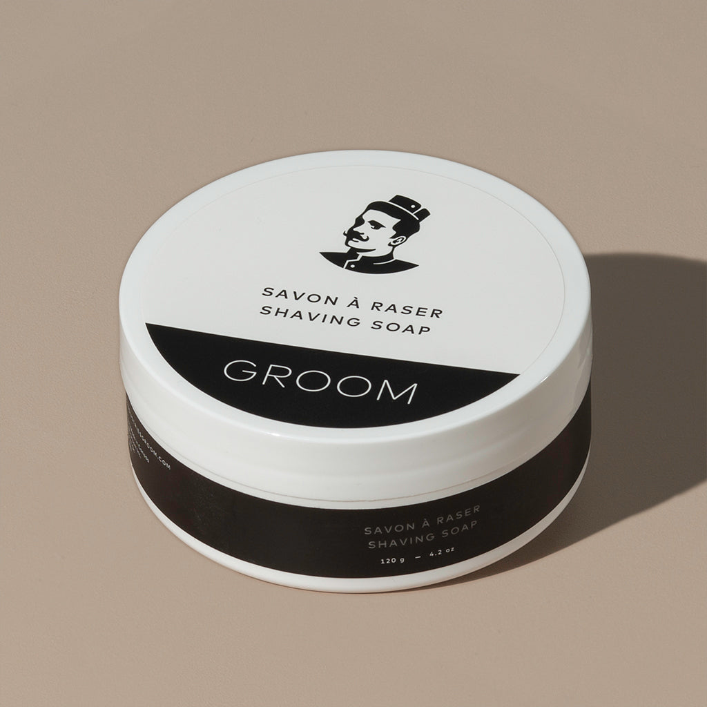 Groom shaving cream in a round white plastic container packaging with a white and black label with a mustache man logo