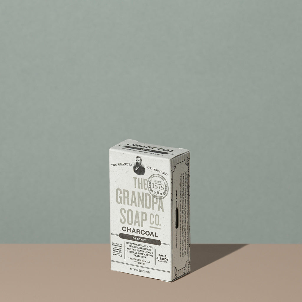 The Grandpa soap Co Charcoal soap bar in a square rectangle light gray cardboard packaging with charcoal writings