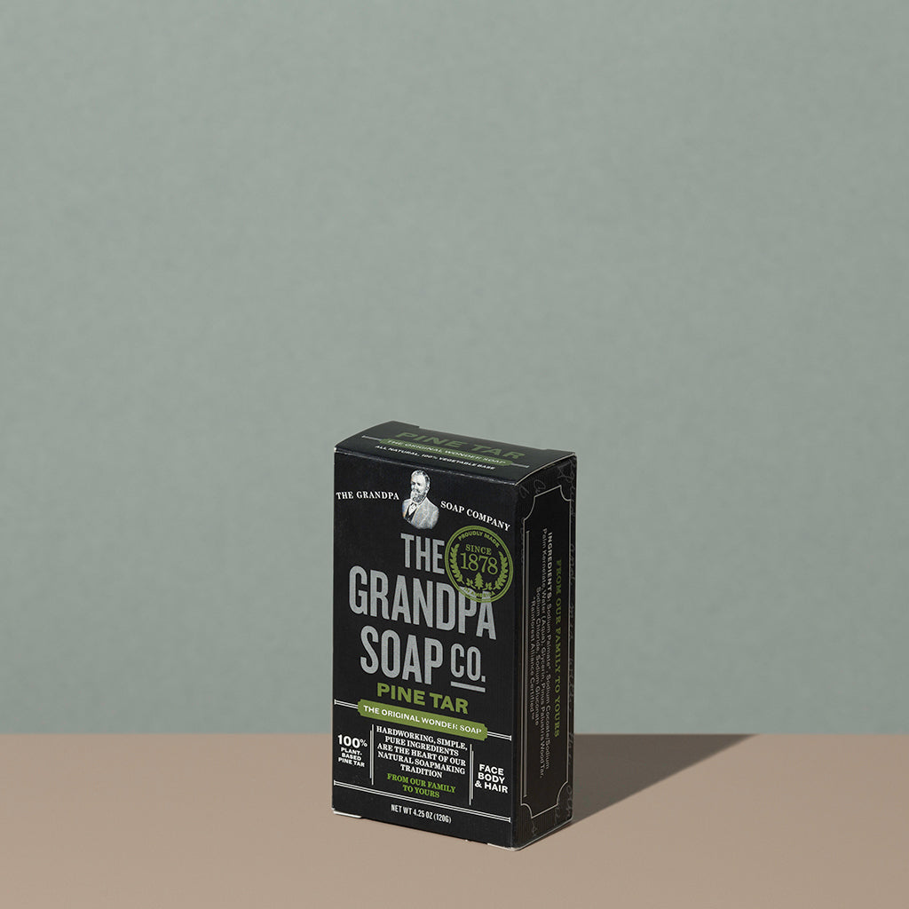 The Grandpa soap Co Pine tar soap bar in a square rectangle black cardboard packaging with white and green writings
