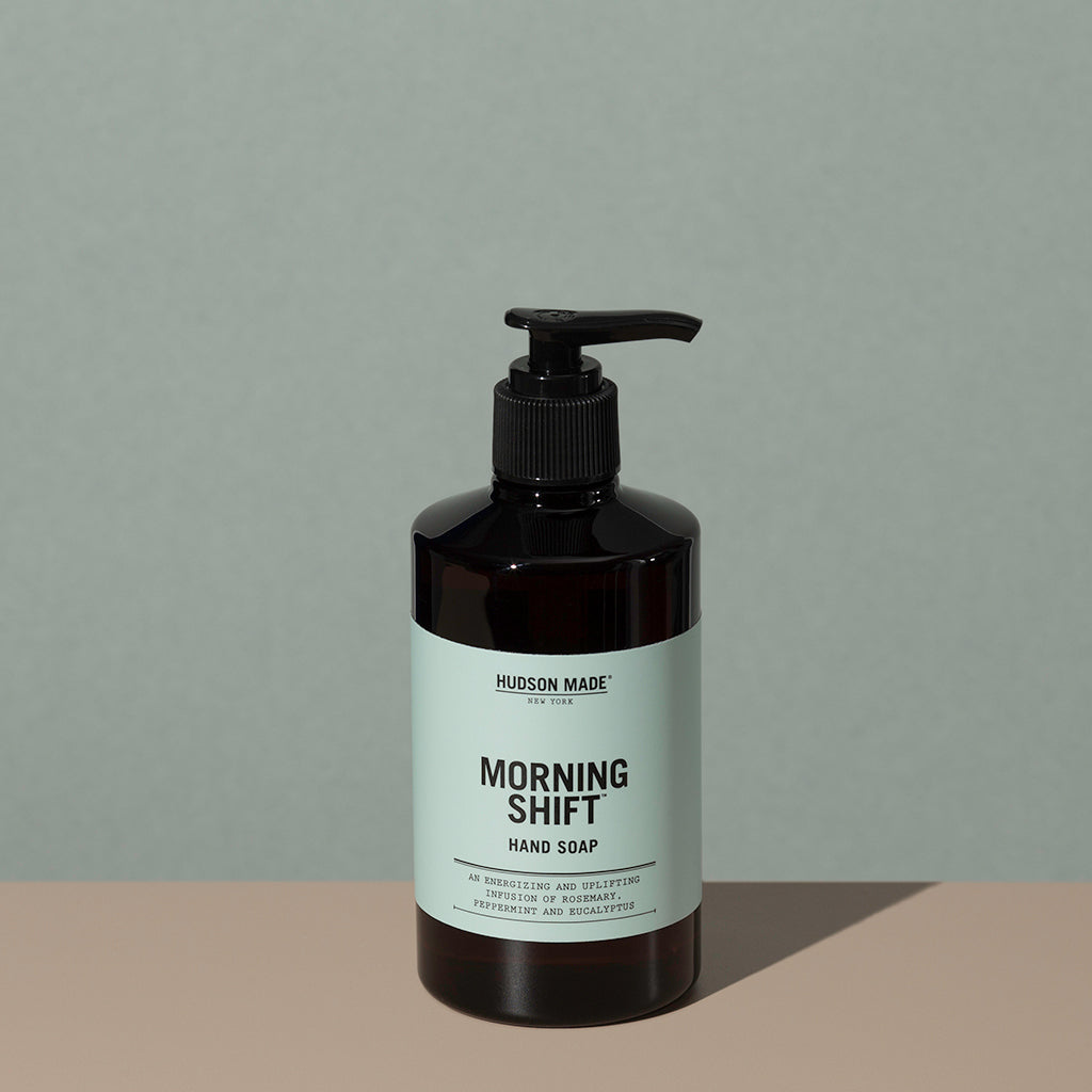 Hudson Made co Morning shift hand soap in a amber rounded cylindric plastic bottle with a black press down dispenser cap and green labeling