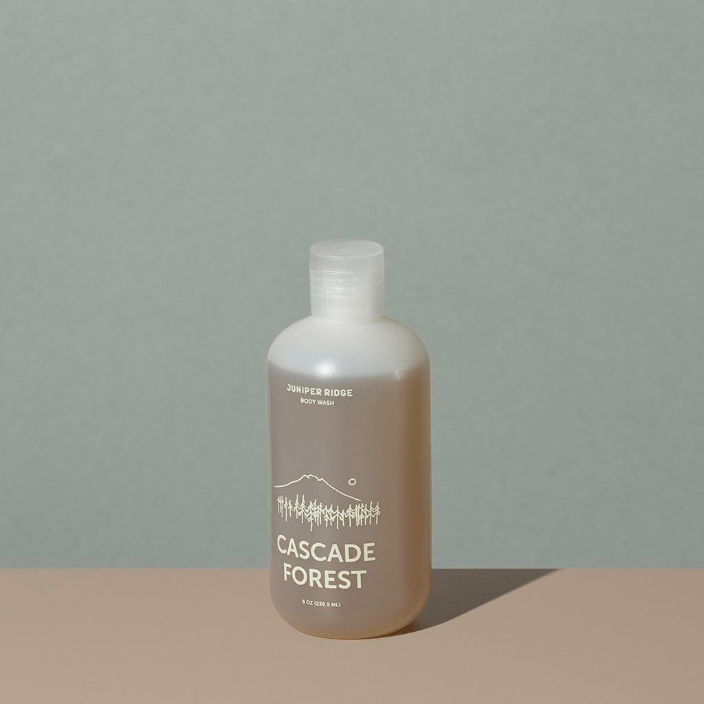 Juniper Ridge cascade forest body wash in an all clear cylindric plastic bottle with a flip top dispenser cap and white labelling of mountain and brand name