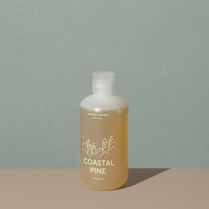 Juniper Ridge coastal pine body wash in an all clear cylindric plastic bottle with a flip top dispenser cap and white labelling of mountains and brand name