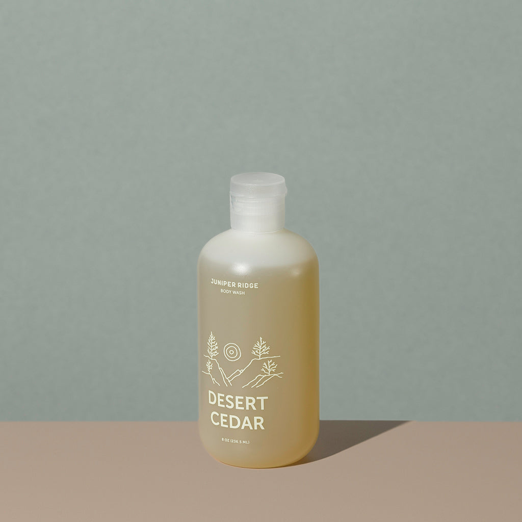 Juniper Ridge desert cedar body wash in an all clear cylindric plastic bottle with a flip top dispenser cap and white labelling of mountain and brand name