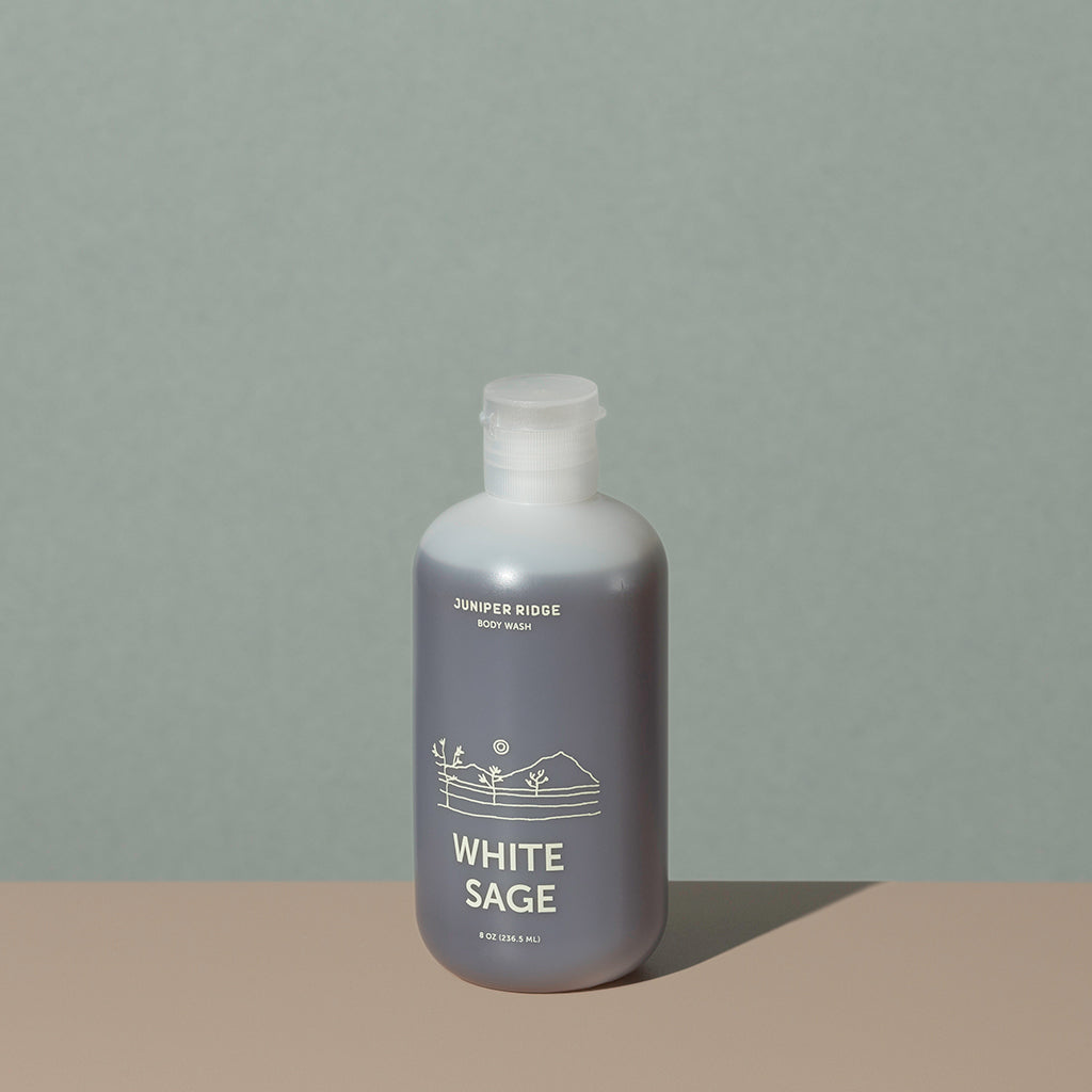 Juniper Ridge White Sage body wash in an all clear cylindric plastic bottle with a flip top dispenser cap and white labelling of mountain and brand name