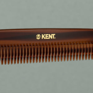 Close up details of tortoise Kent large coarse handcrafted 190mm acetate rounded tooth comb for hair or beard on a table