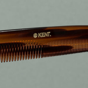Close up details of tortoise Kent fine coarse handcrafted 190mm acetate rounded tooth comb for hair or beard with gold label on a table