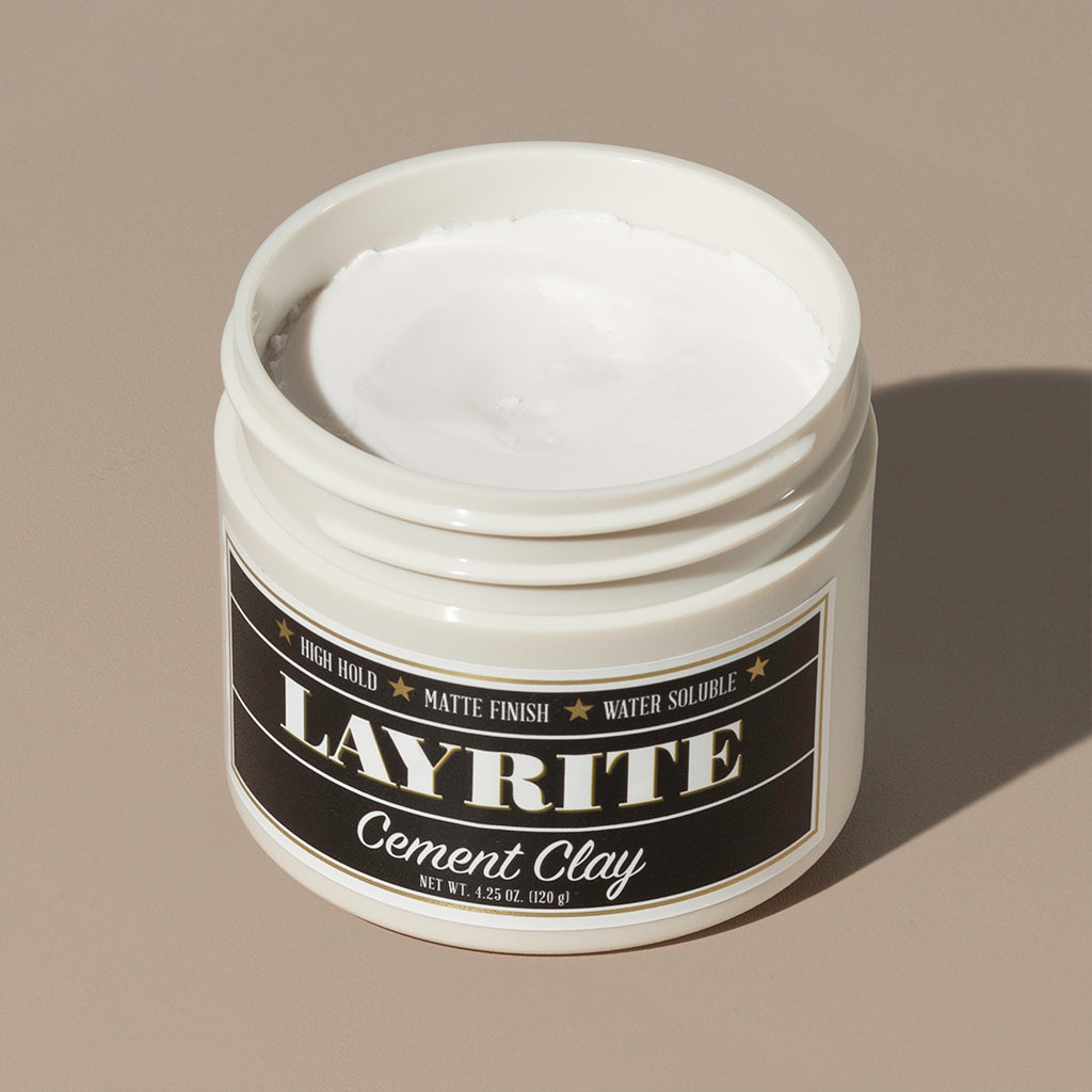 View inside white cream wax Layrite 4.25oz Cement Clay Extreme Hold and Matte Finish hair pomade in a rounded white plastic container with gold twist cap and black label