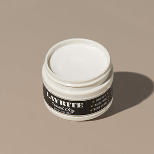 View inside white cream wax Layrite 1.5oz Cement Clay Extreme Hold and Matte Finish hair pomade in a rounded white plastic container with gold twist cap and black label