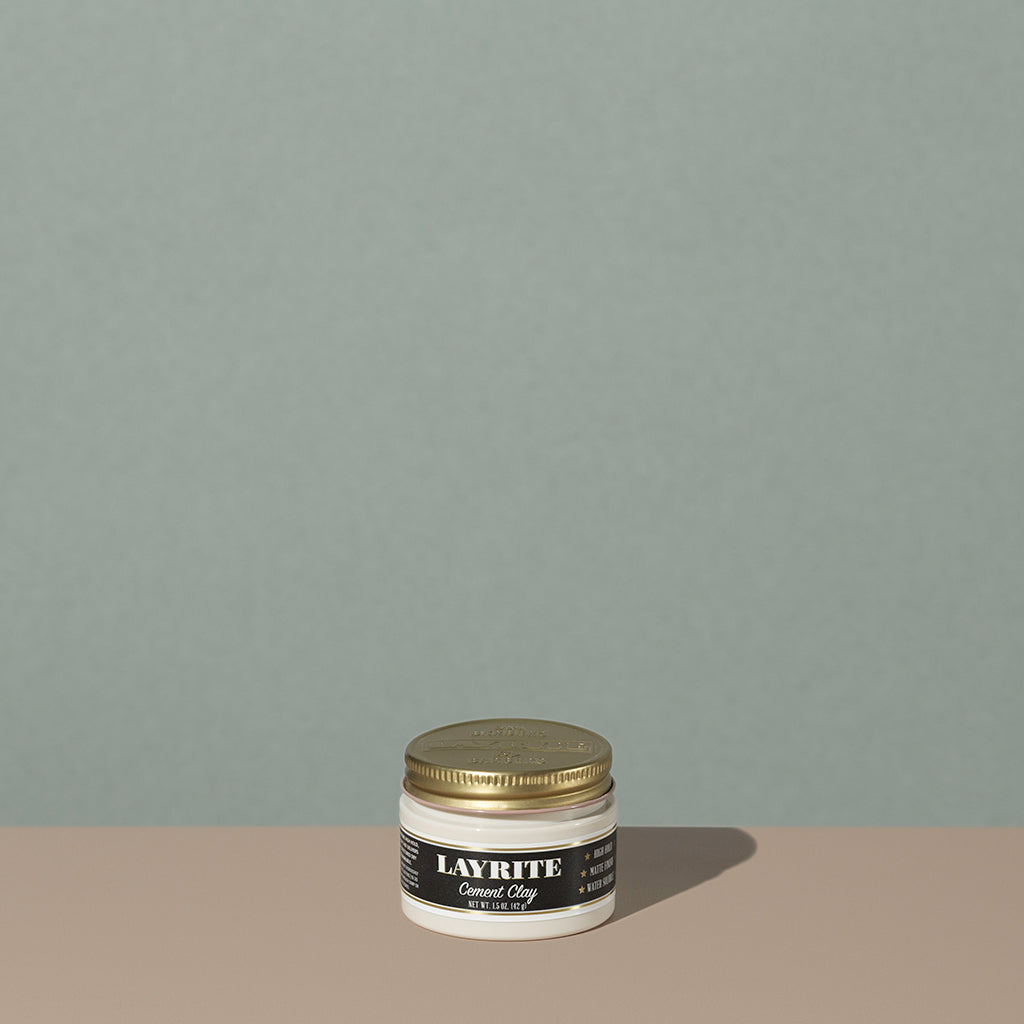 Layrite 1.5oz Cement Clay Extreme Hold and Matte Finish hair pomade in a rounded white plastic container with gold twist cap and black label