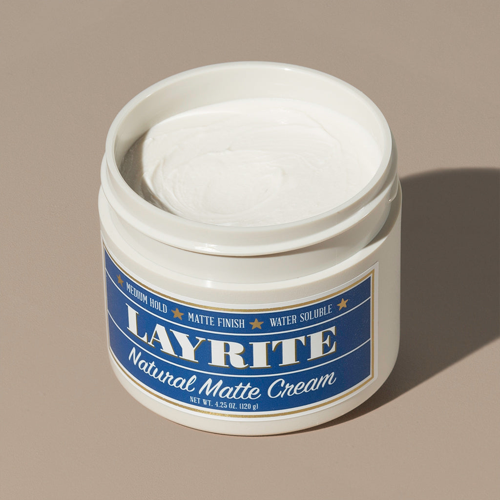 View inside white cream wax Layrite 4.25oz Natural Matte Cream Medium Hold & Natural Finish hair pomade in a rounded white plastic container with gold twist cap and blue label