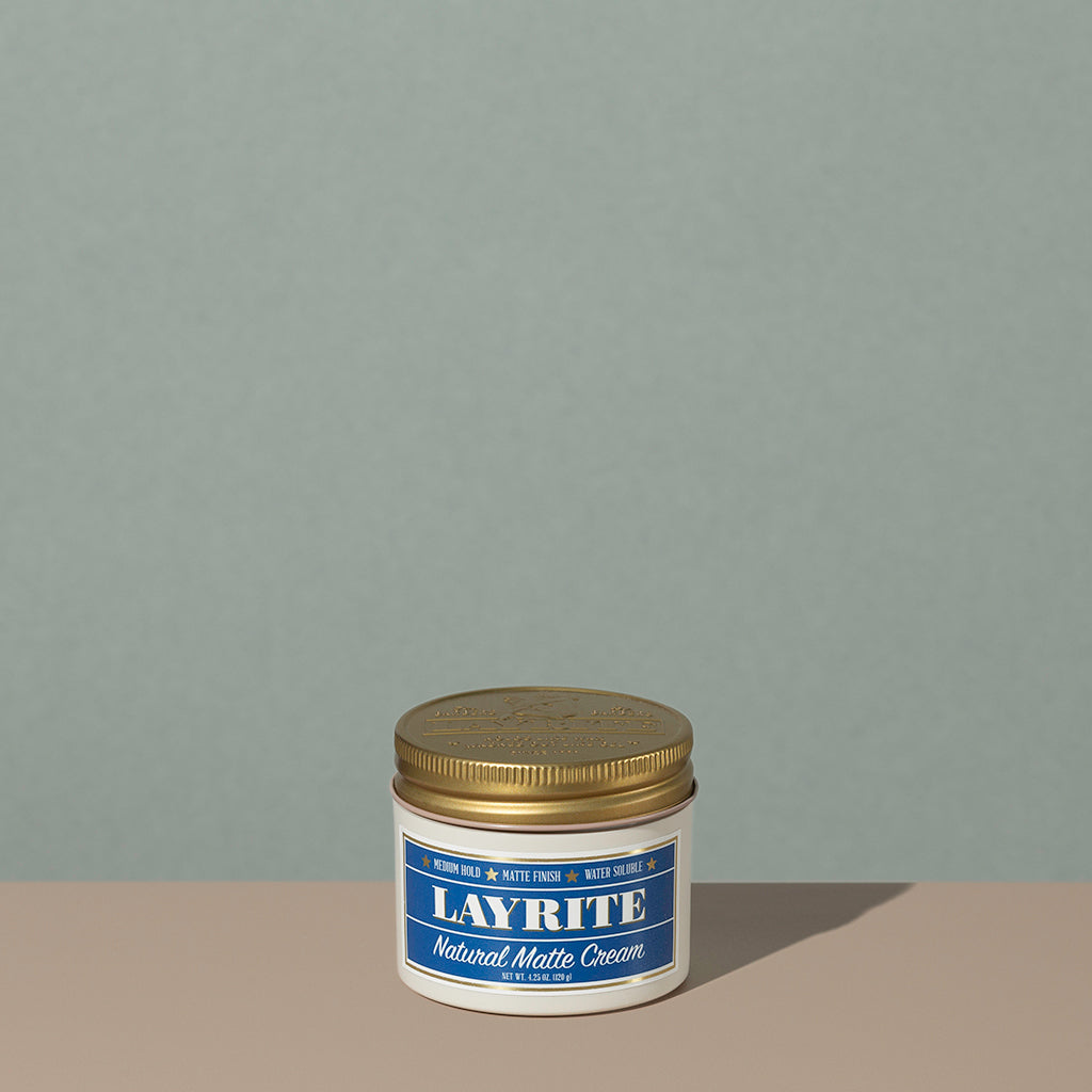 Layrite 4.25oz Natural Matte Cream Medium Hold & Natural Finish hair pomade in a rounded white plastic container with gold twist cap and blue label