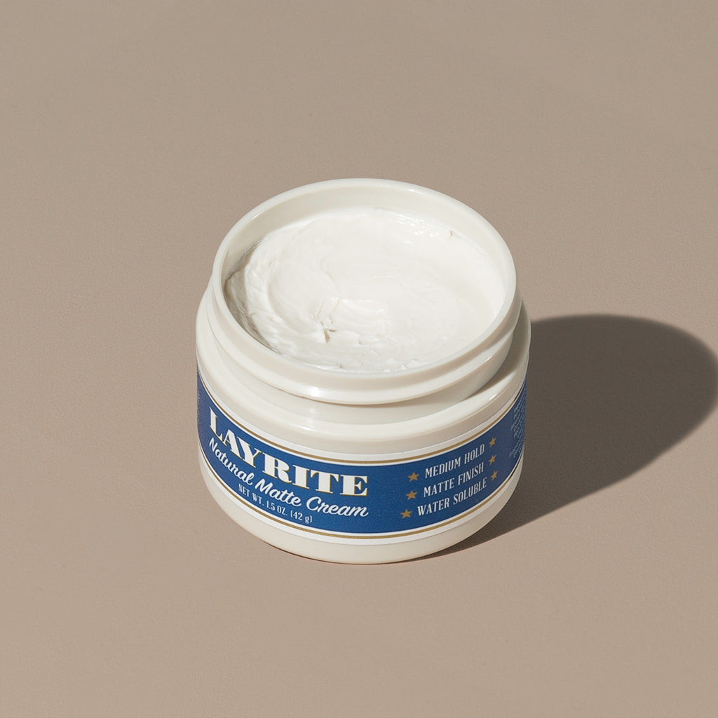View inside white cream wax Layrite 1.5oz Natural Matte Cream Medium Hold & Natural Finish hair pomade in a rounded white plastic container with gold twist cap and blue label