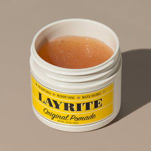 View inside transparent brown wax gel Layrite 4.25oz Original Pomade Medium Hold & Medium Shine hair pomade in a rounded white plastic container with gold twist cap and yellow label