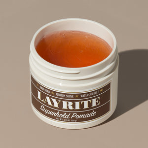 View inside transparent brown wax gel Layrite 4.25oz Superhold Pomade - High Hold & Medium Shine hair pomade in a rounded white plastic container with gold twist cap and brown label