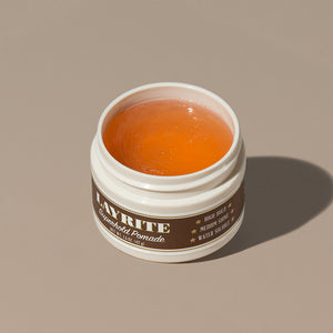 View inside transparent brown gel wax Layrite 1.5oz Superhold Pomade - High Hold & Medium Shine hair pomade in a rounded white plastic container with gold twist cap and brown label
