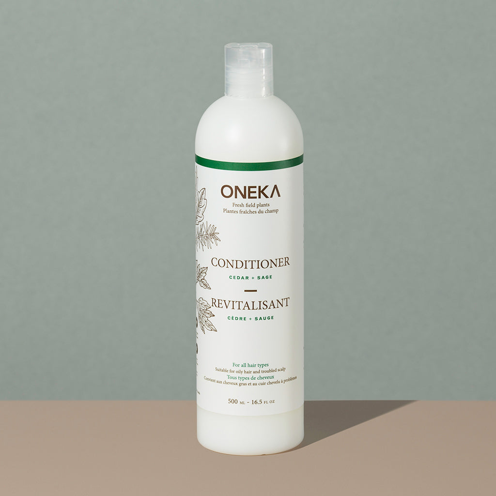 Oneka cedar and sage organic conditionner in a long cylindric clear white plastic bottle with a press cap and white and green labeling