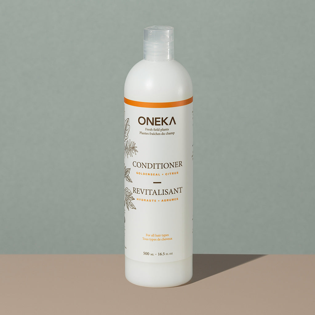 Oneka goldenseal and citrus organic conditionner in a long cylindric clear white plastic bottle with a press cap and white and orange labeling