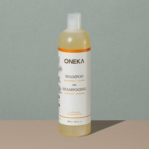 Oneka goldenseal and citrus organic shampoo in a long cylindric clear white plastic bottle with a press cap and white and orange labeling