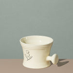 Pure badger shaving porcelain shaving mug with handle in cream with a silver logo