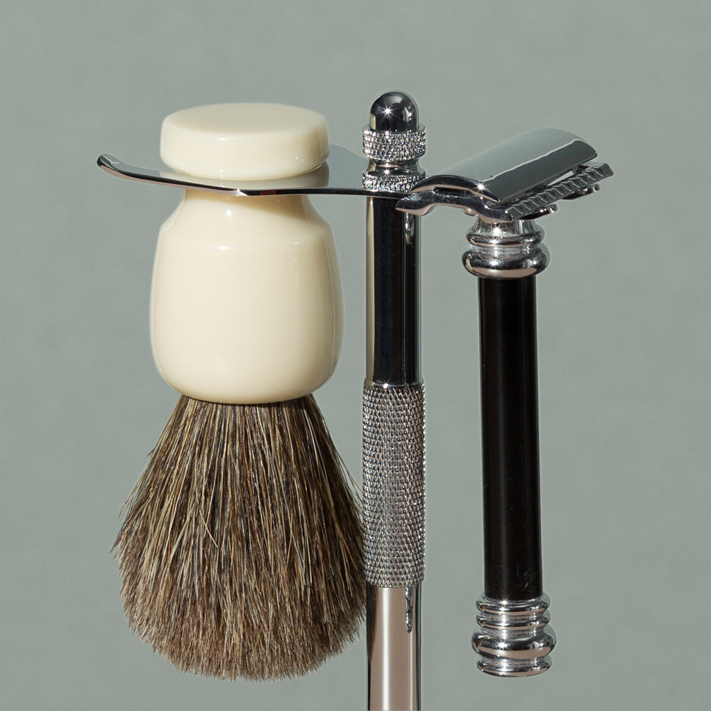Close up on pure badger shaving cream Badger brush and black safety razor stand in chrome stainless steel