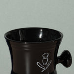 Close up detail of Pure badger shaving porcelain shaving mug with handle in black with a white logo