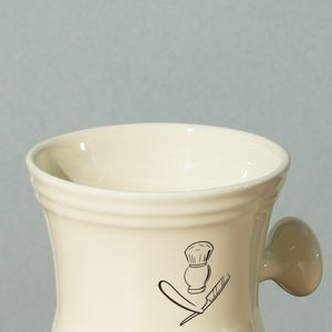 Close up detail of Pure badger shaving porcelain shaving mug with handle in cream with a silver logo