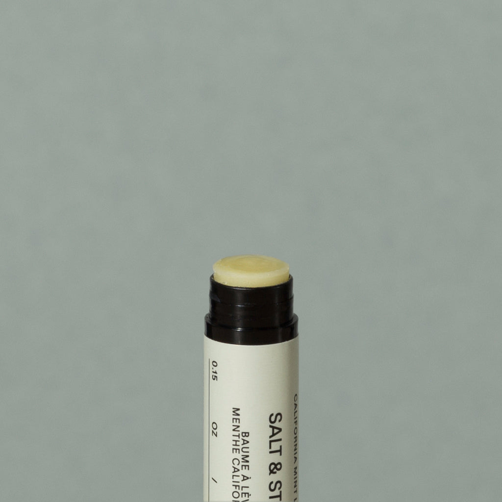 Close up details of yellowish wax Salt & Stone mint lipstick balm in a small cylindric black lipstick packaging with a black cap and off white labeling with black writings