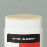 Close up details of creamy wax Thinksport natural deodorant in a white typical rounded square deodorant plastic container with red, black and white logo sticker and a cap