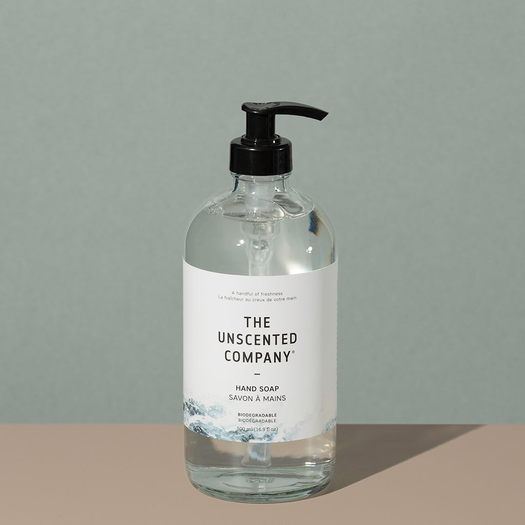 The Unscented Company biodegradable Hand soap in a clear glass bottle with a press down black dispenser cap and a white labeling with black writings and foggy gray mountains